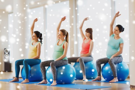 pregnancy, sport, fitness, people and healthy lifestyle concept - group of happy pregnant women exercising on stability ball in gym over snow