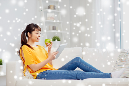 manzana verde: people, healthy eating, education, technology and concept - happy young asian woman sitting on sofa with tablet pc computer and green apple at home over snow Foto de archivo