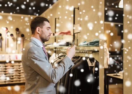 tienda de ropa: venta, compras, moda, tecnología y concepto de la gente - hombre feliz en juego con smartphone elección de la ropa en la tienda de ropa sobre la nieve