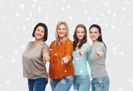 mujeres felices: elección, la amistad, la moda, la gente diversa concepto - grupo de mujeres felices del tamaño más en ropa casual que señala el dedo en usted sobre la nieve Foto de archivo
