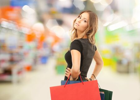 sale and people - woman with colorful shopping bags over supermarket background photo