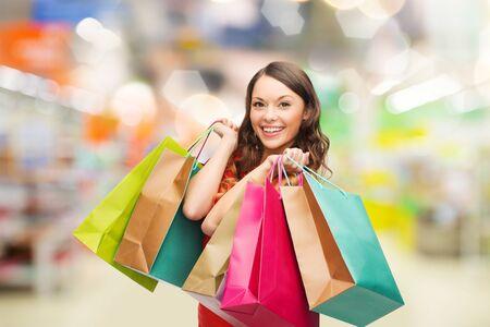 chicas de compras: mujer sonriente con bolsas de colores sobre fondo supermercado - venta y la gente