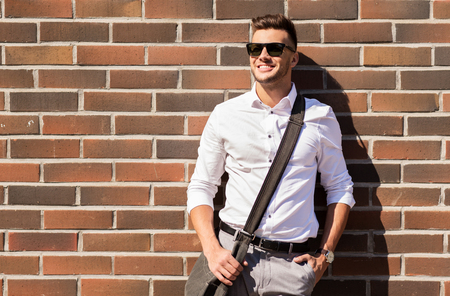 style and people concept - happy smiling young man in sunglasses with bag over brickwall