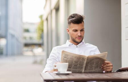 periodical: business, mass media and people concept - smiling man reading newspaper with coffee at city street cafe Stock Photo
