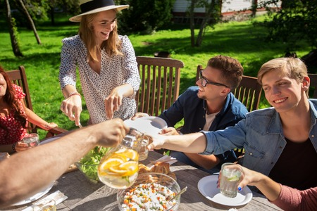 dinner food: leisure, holidays, eating, people and food concept - happy friends having dinner at summer garden party