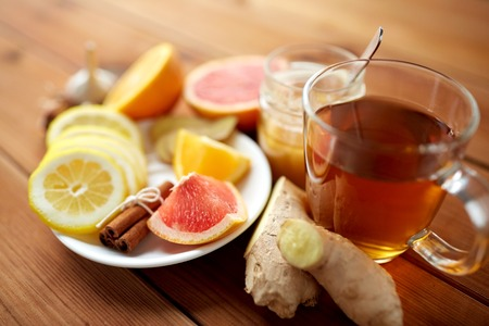 health, traditional medicine, folk remedy and ethnoscience concept - cup of ginger tea with honey, citrus and cinnamon on wooden background Stock Photo
