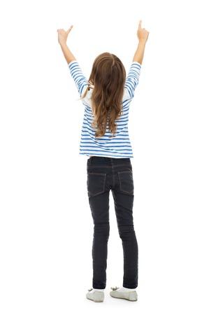 niño empujando: la educación, la gente y concepto de infancia - chica apuntando con el dedo a algo invisible sobre blanco Foto de archivo