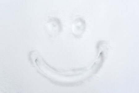 christmas funny: winter holidays and christmas concept - smiley drawing on snow surface Stock Photo