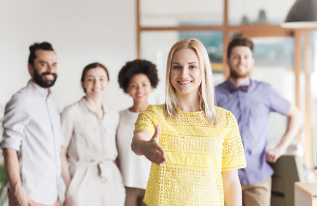 personas saludandose: business, startup, people, gesture and teamwork concept - happy young woman greeting by handshake over creative team in office
