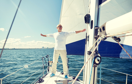 sail boat: sailing, age, tourism, travel and people concept - happy senior man enjoying freedom on sail boat or yacht floating in sea Stock Photo
