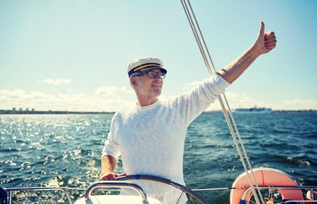 old man happy: sailing, age, tourism, travel and people concept - happy senior man in captain hat on steering wheel and showing thumbs up sail boat or yacht floating in sea