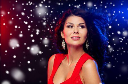 femme brune sexy: les gens, les vacances d'hiver, discothèque, mode de vie nocturne et concept loisirs - belle femme sexy en robe rouge à boîte de nuit sur la neige