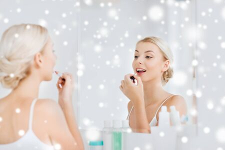 coloring lips: beauty, make up, cosmetics, morning and people concept - smiling young woman coloring her lips with lipstick  looking to mirror at home bathroom over snow Stock Photo