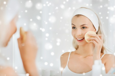 purifying: beauty, skin care and people concept - smiling young woman   in hairband washing her face with facial cleansing sponge at bathroom over snow