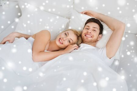 enamorados en la cama: people, rest, love, relationships and happiness concept - happy smiling couple lying in bed at home over snow
