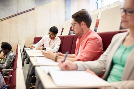 la educación, la escuela secundaria, la universidad, el aprendizaje y el concepto de la gente - grupo de estudiantes internacionales con los cuadernos de escritura en la sala de conferencias