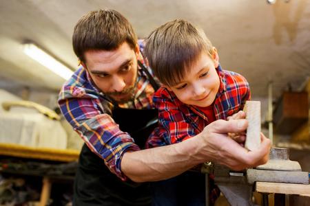 famiglia, falegnameria, lavorazione del legno e la gente concept - padre e figlio piccolo lavorando con listoni di legno al workshop Archivio Fotografico