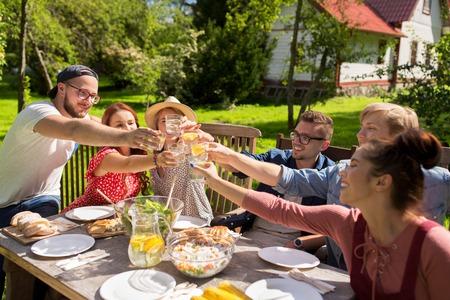 레저, 휴일, 식사, 사람과 식품 개념 - 여름 정원 파티에서 저녁 식사를 행복 친구
