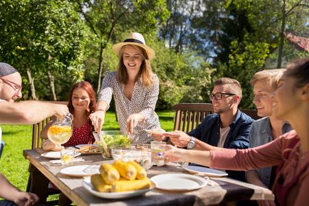 Freizeit, Urlaub, Essen, Menschen und Food-Konzept - glückliche Freunde Abendessen im Sommergarten-Party Standard-Bild - 66984322