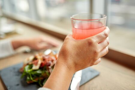 food, drink, eating and people concept - hand with glass of juice and salad at restaurant Stock Photo