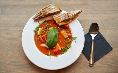 food, dinner, culinary, haute cuisine and cooking concept - plate of delicious gazpacho soup at restaurant Stock Photo