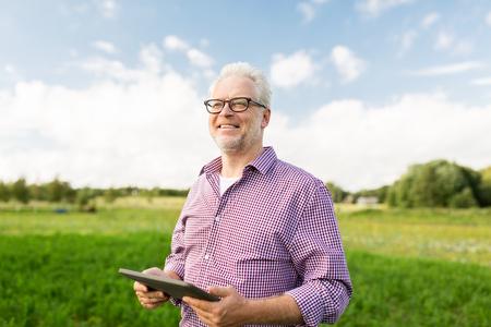 la agricultura, la agricultura, la tecnología, la vejez y las personas concepto - hombre mayor feliz con el ordenador de la PC de la tableta en el condado o de la granja Foto de archivo