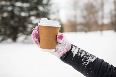 hand holding: people, season, drinks and leisure concept - close up of woman hand with coffee cup outdoors in winter