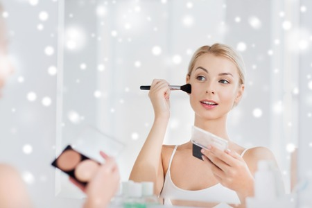 beauty, make up, cosmetics, morning and people concept - young woman with makeup brush and contouring and highlighting palette looking to mirror at home bathroom over snow