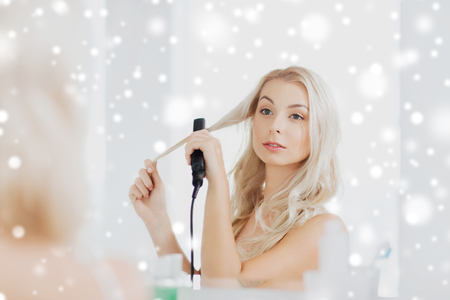 styler: beauty, hairstyle, morning and people concept - smiling young woman with styling iron straightening her hair and looking to mirror at home bathroom over snow