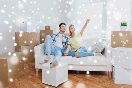 people, repair and real estate concept - smiling couple with boxes moving to new home and dreaming over snow Stock Photo