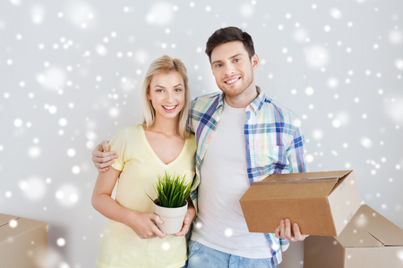 home, people, moving and real estate concept - smiling couple with big cardboard boxes and plant at new place over snow