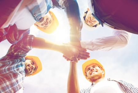 business, building, partnership, gesture and people concept - close up of smiling builders in hardhats with hands on top outdoors Foto de archivo