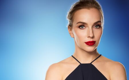 femme fatale: people, luxury and fashion concept - beautiful woman in black with red lips over blue background