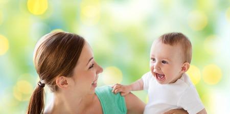 la familia, la maternidad, la paternidad del niño y el concepto - feliz madre joven sonriente con el pequeño bebé sobre fondo verde luces Foto de archivo