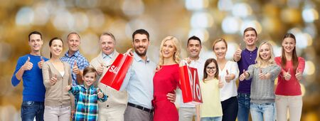 happy shopping: sale, family, generation and people concept - group of happy men and women with shopping bags showing thumbs up over holidays lights background Stock Photo
