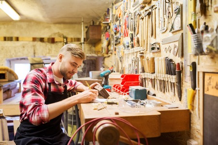 profession, carpentry, woodwork and people concept - carpenter with wood plank and notebook working at workshop Stock Photo