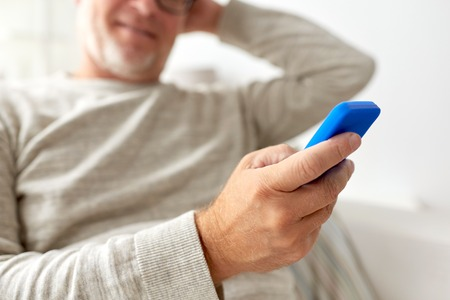 old hand: technology, people, lifestyle and communication concept - close up of happy senior man dialing phone number and texting on smartphone at home Stock Photo
