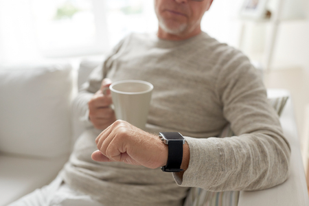 puntualidad: time, morning and people concept - close up of senior man with coffee or tea mug looking at wristwatch at home