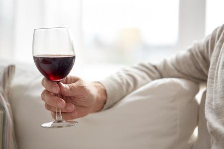 사람들, 알코올 및 음료 개념 - 집에서 레드 와인과 유리를 잡고 수석 사람 손을 가까이