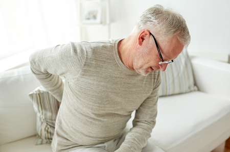 back ache: people, healthcare and problem concept - unhappy senior man suffering from pain in back or reins at home Stock Photo