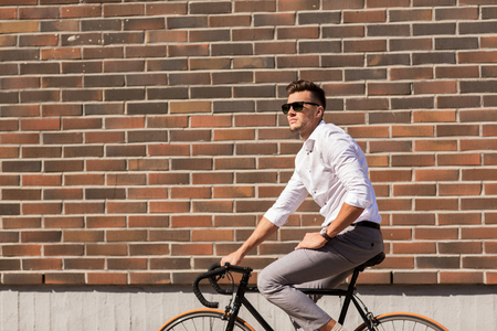 metrosexual: lifestyle, transport and people concept - young man in sunglasses riding bicycle on city street over brickwall Stock Photo