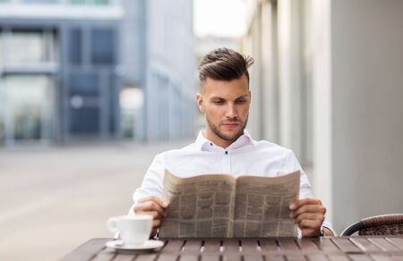 mass media: business, mass media and people concept - smiling man reading newspaper with coffee at city street cafe Stock Photo