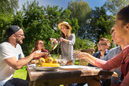 picnic table: leisure, holidays, eating, people and food concept - happy friends having dinner and sharing salad at summer garden party