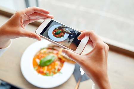 food, eating, technology, culinary and people concept - woman hands with smartphone photographing gazpacho soup at restaurant Stock Photo