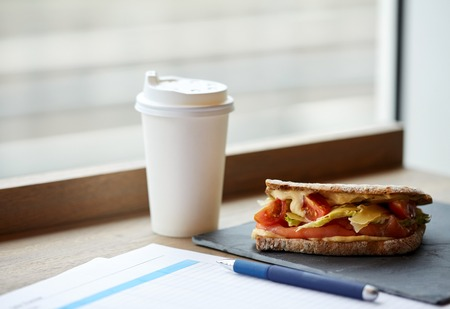 lunch table: business lunch, food, dinner and eating concept - salmon panini sandwich with tomatoes and cheese, cup of drink and papers on cafe table Stock Photo