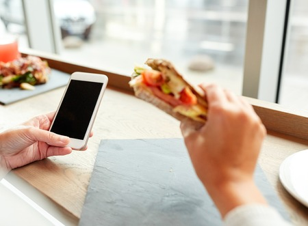 panino: food, dinner, technology and people concept - woman with smartphone eating salmon panini sandwich with tomatoes and cheese at restaurant
