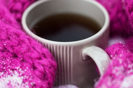 cosiness: season, drinks, christmas and winter holidays concept - close up of tea or coffee mug and knitted woolen scarf in snow Stock Photo