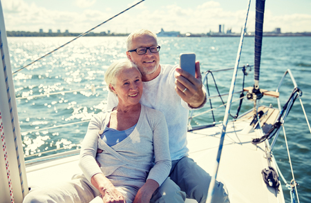 family vacation: sailing, technology, tourism, travel and people concept - happy senior couple with smartphone taking selfie on sail boat or yacht deck floating in sea