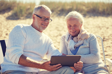 family vacation: family, age, travel, tourism and people concept - happy senior couple with tablet pc computer resting in folding chairs on summer beach Stock Photo
