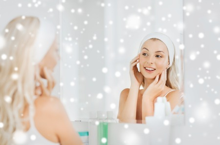 beauty skin: beauty, skin care and people concept - smiling young woman in hairband touching her face and looking to mirror at home bathroom over snow